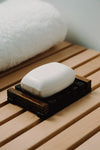 one bar of white soap lays in a wooden holder