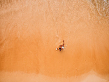 one man lounges on the beach at the water's edge