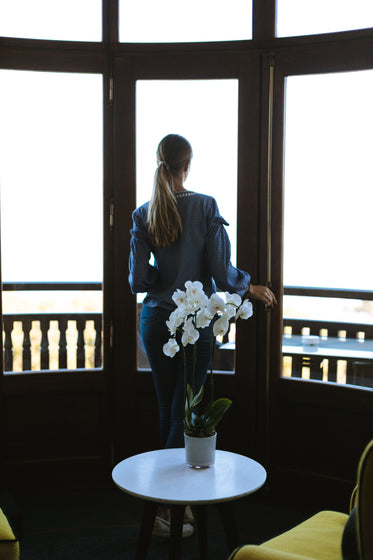 orchid decor and woman enjoying view