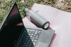 outdoors laptop and water bottle lay on pink yoga mat