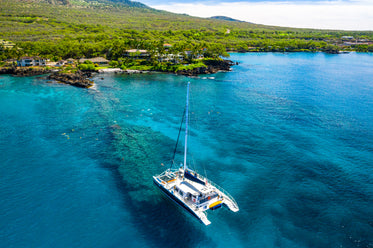 overhead view of sailboat anchored on coral reef