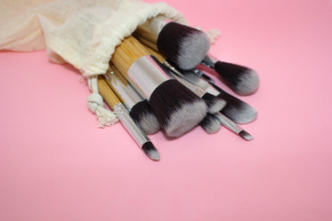 paintbrushes of different sizes spill onto a pink table