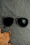 pair of silver framed sunglasses on a stone surface