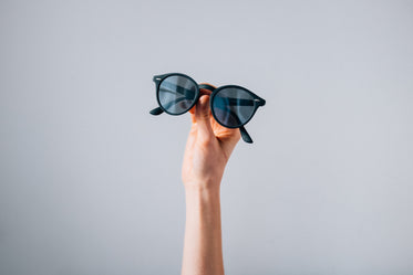 pair of sunglasses held in front of grey background