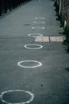 paved sidewalk with white painted circles