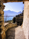 paved walkway by lake and mountains