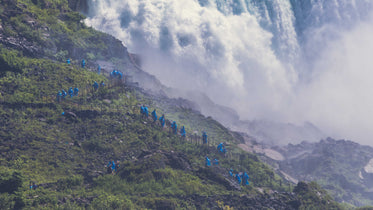 people hiking by waterfall