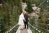 people hold hands walking down a suspension bridge