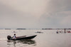 people kayak on a cloudy day with a boat following