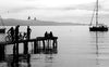people on a dock and nearby boat in black and white