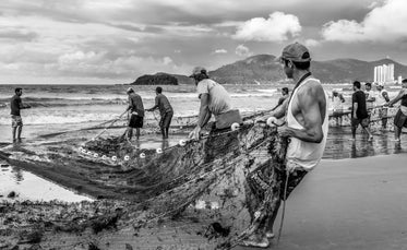 people pulling a fishing net to shore in black and white