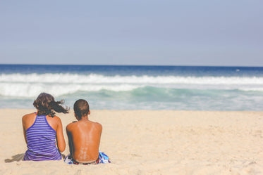 people sit on the beach and look out toward ocean