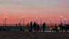 people stand on beach by a pier at sunset