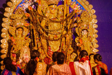 people stand with statue of durga maa