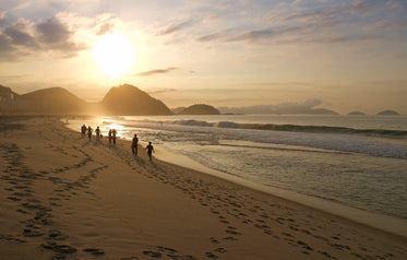 people walking down a sandy beach at sunset
