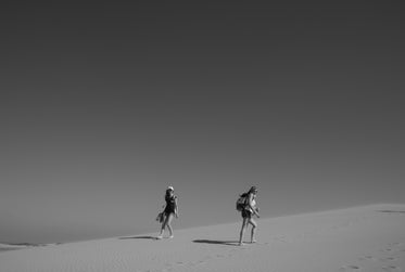 people walking in the desert in black and white
