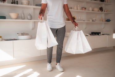 peron holds white paper bags in both hands
