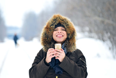 person bundled for winter sticks out tongue