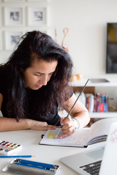 person carefully paints in a sketchbook