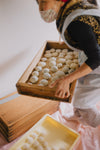 person carries a wooden box full of dough balls