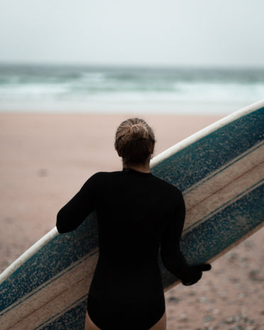 person carries their blue and white surfboard to the ocean