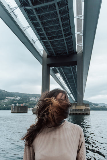 person covered by hair stands under bridge on a windy day