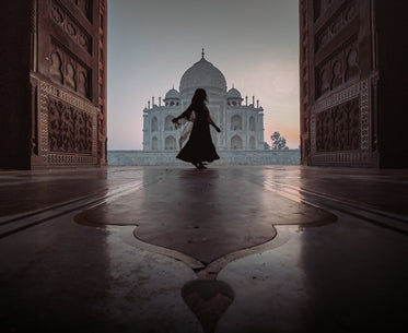 person dances in door way with a view of the taj mahal
