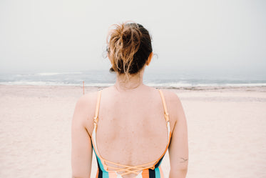 person facing wavy water on a sandy beach