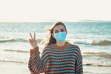 person gives peace sign while wearing a facemask