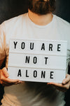 person holding a sign that says you are not alone