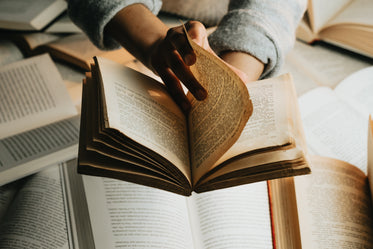 person holds a book over a stack and turns the page