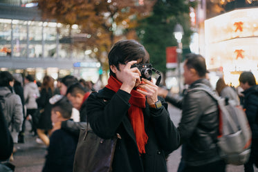 person holds a camera up and takes a picture outdoors