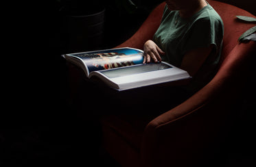 person holds a large book on their lap and reads