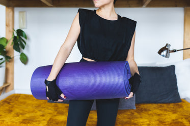 person holds a rolled up yoga mat under arm