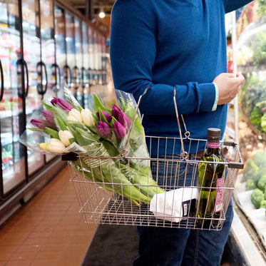 person holds a silver shopping basket carrying tulips