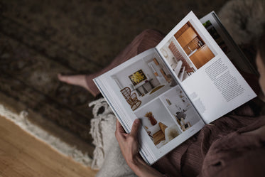 person holds an interior design book on their lap