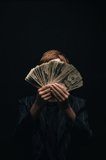 person holds money in front of face
