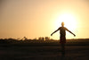 person holds out arms silhouetted by a setting sun