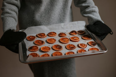 person holds silver baking tray filled with baked oranges