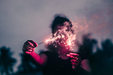 person holds sparklers out blocking their face