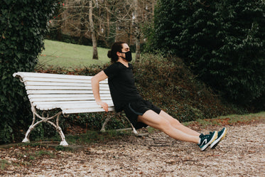 person holds the edge of a bench while stretching