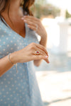 person holds their hand forward displaying a diamond ring