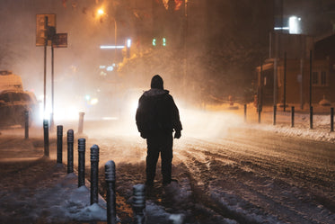 person illuminated by street lights during a snow storm