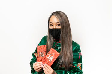 person in a facemask holds red metallic cards
