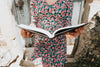 person in a floral dress holds a large book open