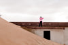 person in a pink jacket stands on sand covered building
