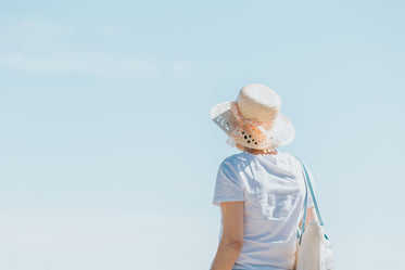 person in a straw hat faces toward a blue sky