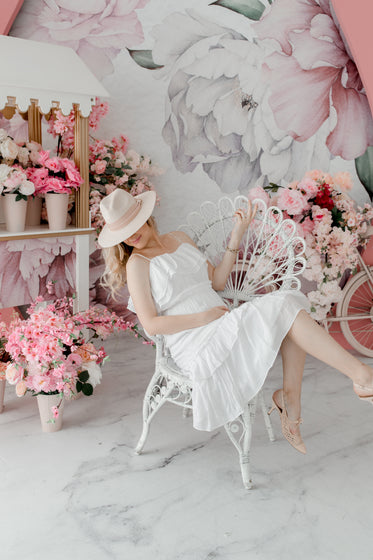 person in a white dress and hat sits in a floral room