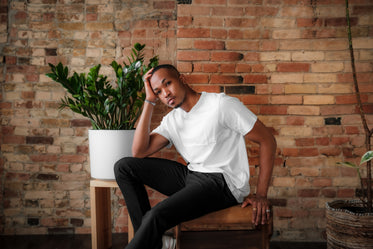 person in a white shirt sits in front of a brick wall