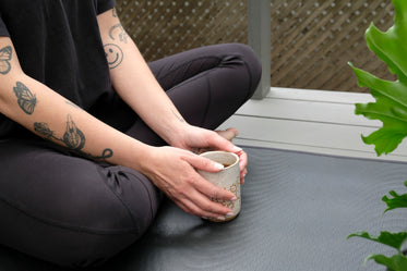 person in athletic wear with a mug with both hands